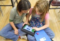 Students in the classroom with an iPad